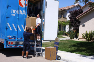 A photograph of two movers unloading boxes from a northAmerican moving van