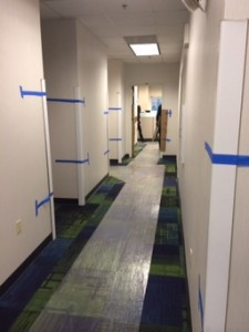 A photograph of an office hallway with protective plastic on the carpet
