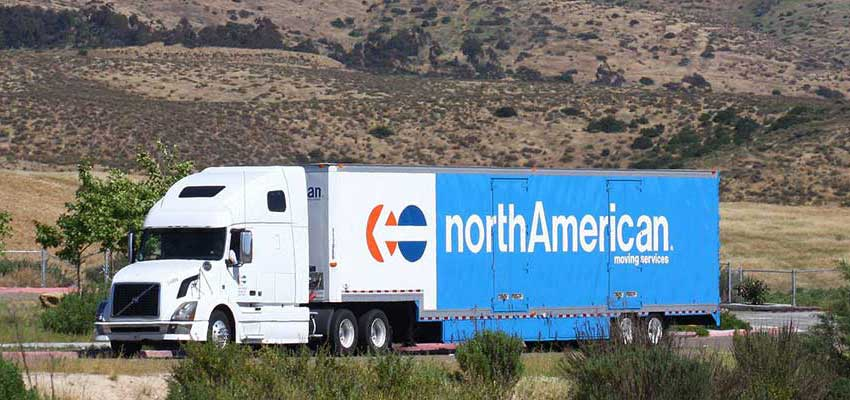 A photograph of a northAmerican moving truck on the open road