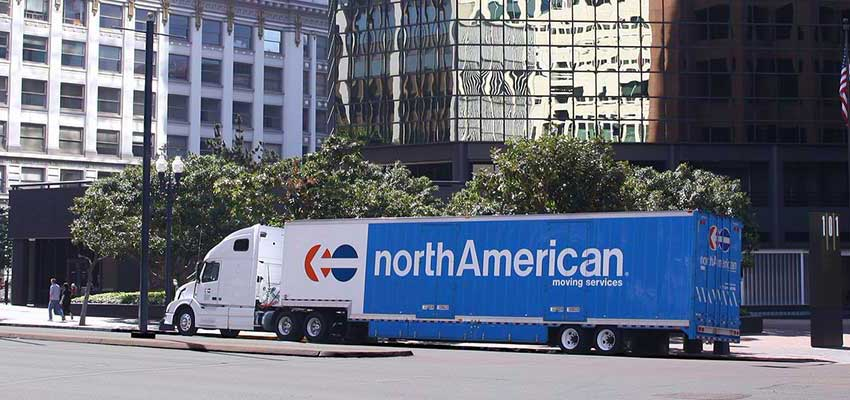 A photograph of a northAmerican moving truck parked in front of an office building