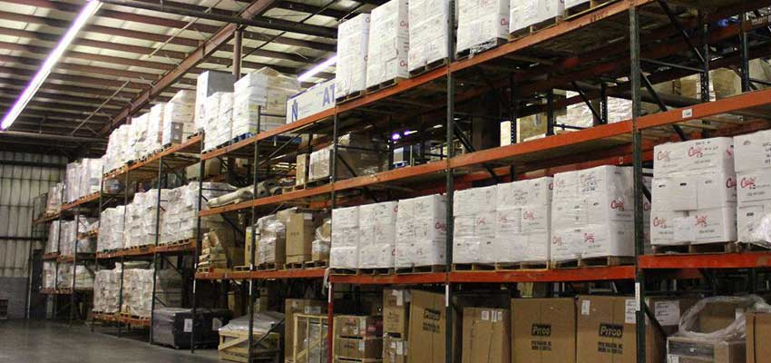 A photograph of shelves loaded with packing boxes in a warehouse