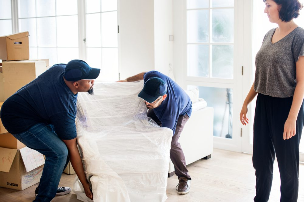 woman supervising professional movers from a moving company